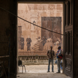 January 8, 2016 - Havana, Cuba: Two men stand in the doorway of apartment building across from a large mural depicting Cuban history. (Liz Roll/Polaris)